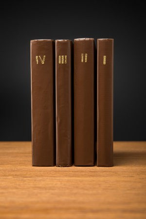 volumes of retro books in leather brown covers on wooden table isolated on black