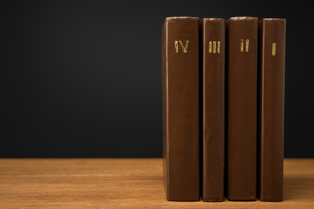 volumes of vintage books in leather brown covers on wooden table isolated on black