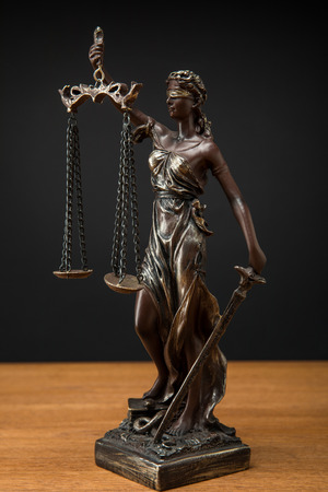 bronze statuette with scales of justice on wooden table isolated on black