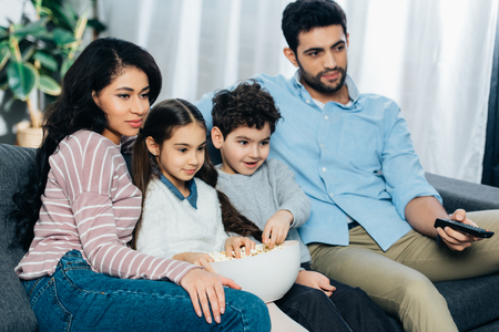 happy hispanic family watching tv with popcorn bowl at home
