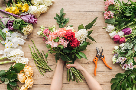 Cropped view of florist holding flower bouquet on wooden table