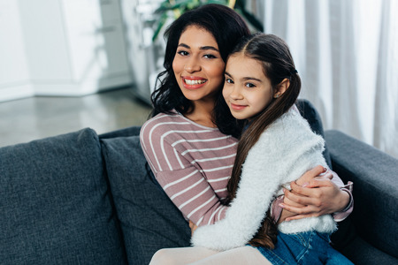 latin woman hugging cute daughter while sitting on sofa at home