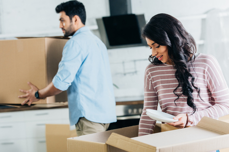 selective focus of attractive latin woman holding plates near boxes with husband on background