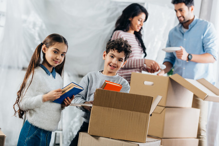 selective focus of cute kids holding books while parents standing near boxes on background