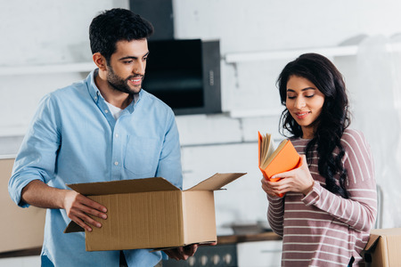 attractive latin woman holding book while standing near husband with box in new home Stock Photo