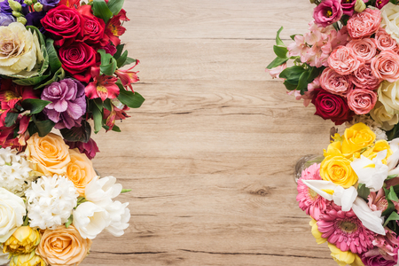 Top view of fresh colorful flowers on wooden surface