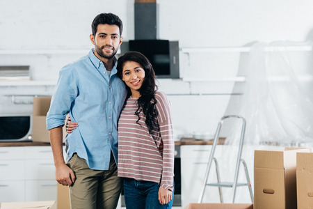 cheerful latin couple embracing and smiling near boxes in new home