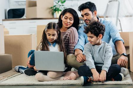vrolijke latino-familie die naar laptop kijkt terwijl ze op tapijt zit in een nieuw huis