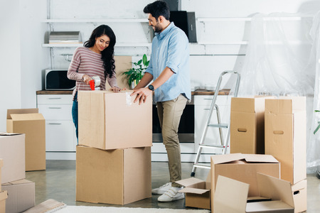 cheerful latin couple packing boxes while moving to new home Stock Photo