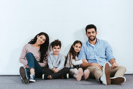 cheerful hispanic family smiling while sitting on floor near white wall Stock Photo