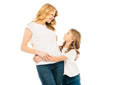 cute child and beautiful mother hugging and looking at each other isolated on white