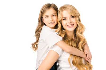 smiling mother piggybacking cute daughter isolated on white