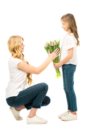 squatting taking beautiful bouquet of tulips from daughter isolated on white
