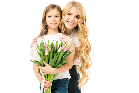 happy mother embracing adorable daughter holding bouquet of pink tulips isolated on white 版權商用圖片