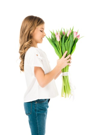 cute child enjoying flavor of beautiful pink tulips isolated on white