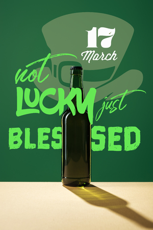 glass beer bottle with not lucky just blessed lettering on green background
