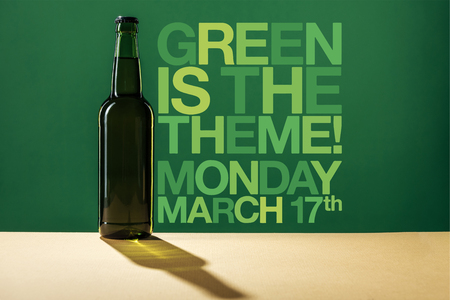 glass beer bottle near green is the theme lettering on green background