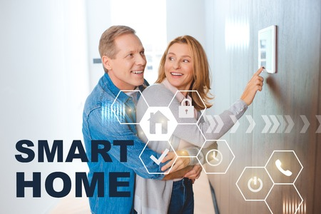happy man hugging wife using smart house system control panel, smart home concept