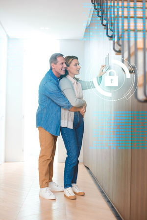 husband hugging wife using smart house system control panel