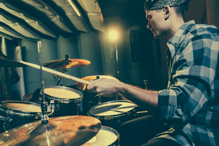 selective focus of drummer holding drum sticks while playing drums Фото со стока