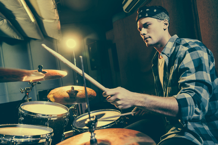 selective focus of handsome drummer holding drum sticks while playing drums