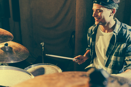 selective focus of cheerful drummer holding drum sticks while playing drums