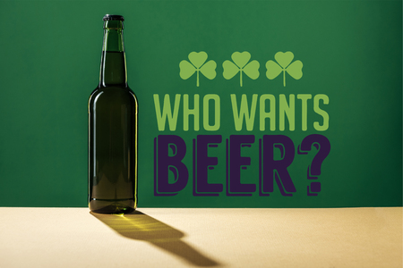 glass beer bottle near who wants beer lettering on green background Stockfoto - 119588866