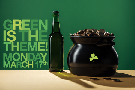 beer bottle and black pot with golden coins near green is the theme lettering on green background Stock Photo