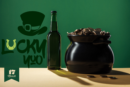 beer bottle and black pot with golden coins near lucky you lettering on green background Banco de Imagens