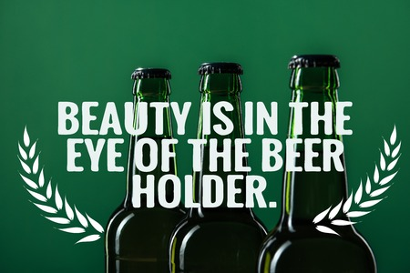 beer bottles near beauty is in the eye of the beer holder lettering on green background