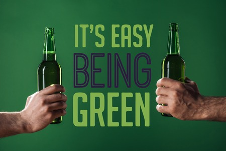 cropped view of men holding beer bottles near its easy being green lettering on green background