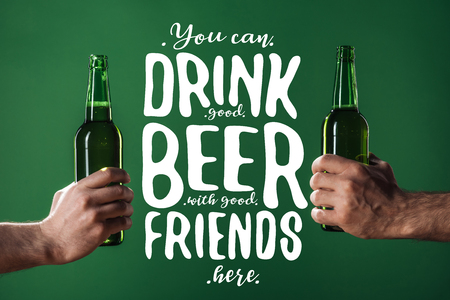 cropped view of men holding beer bottles near you can drink good beer with good friends here lettering on green background Stock Photo