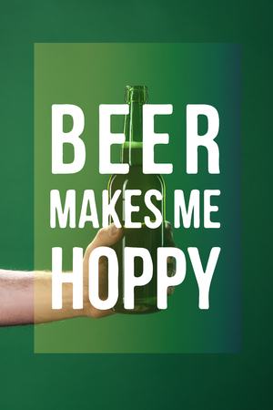 cropped view of man holding beer bottle near beer makes me hoppy lettering on green background