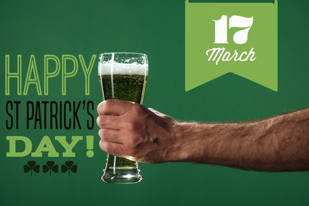 cropped view of man holding glass of beer with foam near happy st patricks day lettering on green background 스톡 콘텐츠