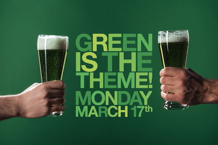 cropped view of men holding glasses of beer with foam near green is the theme lettering on green background