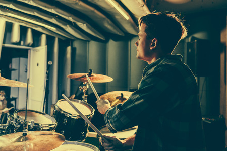 good-looking musician holding drum sticks while playing drums Stock Photo