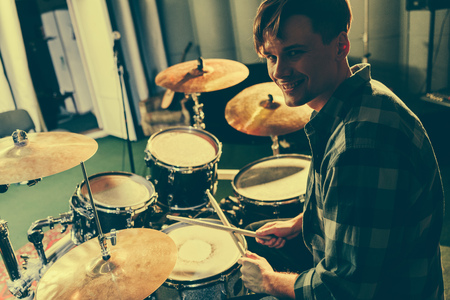 cheerful good-looking musician holding drum sticks near drums