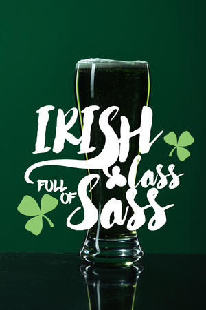 glass of beer with foam near irish lass full of sass lettering on green background