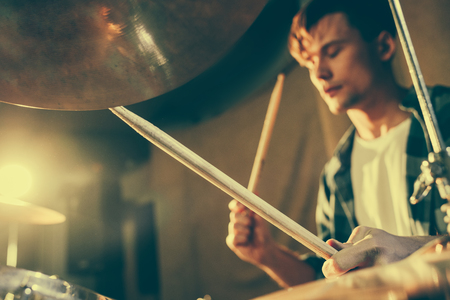 selective focus of drum sticks in hands of young drummer
