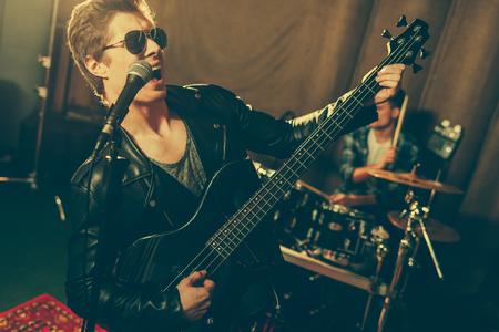 selective focus of guitarist playing electric guitar and singing near drummer 版權商用圖片