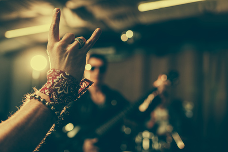selective focus of man showing rock sign near musician
