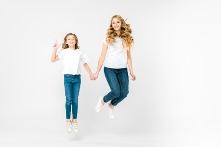 happy mother with adorable daughter jumping on white background 스톡 콘텐츠