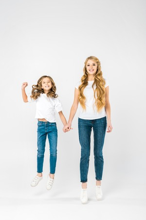 carefree child jumping while holding mothers hand on white background