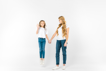 happy daughter jumping and waving hand while holding mothers hand on white background Stockfoto