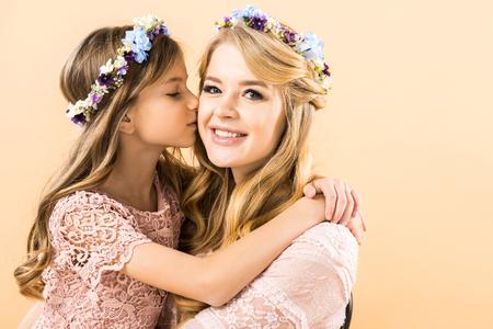 süßes Kind, das glückliche Mutter auf gelbem Hintergrund küsst und umarmt