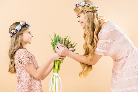 cute daughter gifting bouquet of pink tulips to happy mother on yellow background Reklamní fotografie