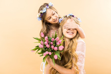 happy mother holding bouquet of pink tulips while cheerful child closing her eyes with hand on yellow background
