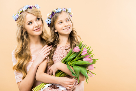 beautiful mother and adorable daughter in floral wreaths looking away and smiling on yellow background