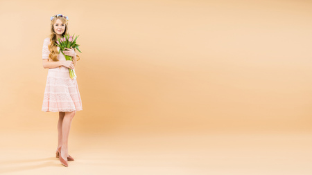 attractive woman in delicate lacy dress and floral wreath holding bouquet of pink tulips on yellow background with copy space
