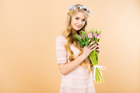 beautiful woman in pink lacy dress and floral wreath holding bouquet of pink tulips and looking at camera on yellow background Stock Photo